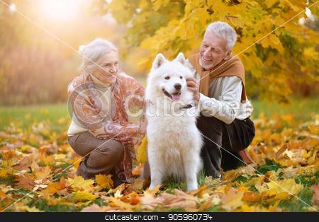portrait of beautiful caucasian senior couple with dog  stock photo, portrait of beautiful caucasian senior couple with dog in autumn park by Ruslan Huzau