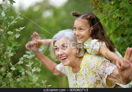 Portrait of grandmother and granddaughter stock photo, Portrait of grandmother and granddaughter in summer park by Ruslan Huzau