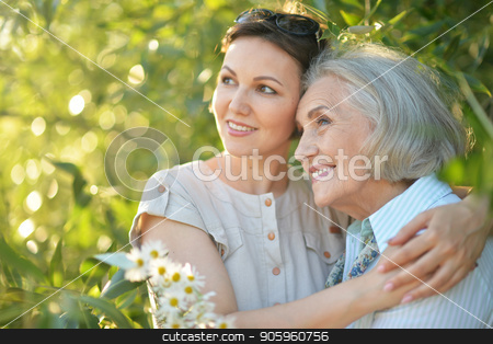 cheerful mother and adult daughter stock photo, Happy senior mother and adult daughter posing together outdoors by Ruslan Huzau