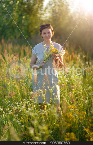 Beuatiful young woman holding wildflowers stock photo, Beuatiful young woman holding wildflowers while standing on green meadow by Ruslan Huzau