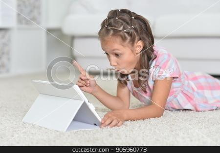 Cute girl with digital tablet on floor stock photo, Portrait of cute girl with digital tablet on floor by Ruslan Huzau