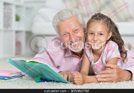 Father helping son with homework  stock photo, Grandfather helping his granddaughter to do homework at home by Ruslan Huzau