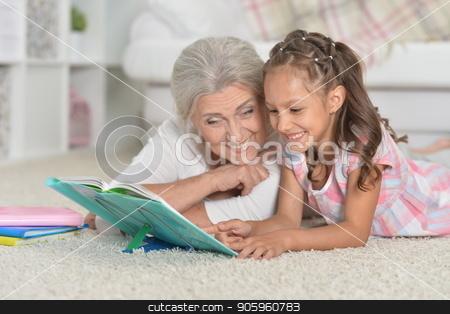 Grandmother with cute little girl doing homework together while  stock photo, Grandmother with cute little girl doing homework together while lying on floor by Ruslan Huzau