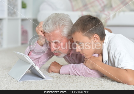 Grandfather with grandson using tablet while lying on floor  stock photo, Grandfather with grandson using tablet while lying on floor at home by Ruslan Huzau