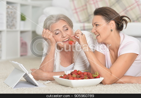 Mother and her adult daughter lying on floor with tablet while e stock photo, Mother and her adult daughter lying on floor with tablet while eating fresh strawberries by Ruslan Huzau