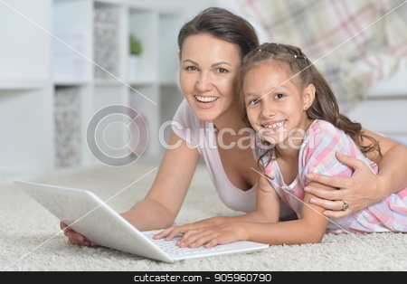 Mother and daughter using laptop together while lying on floor stock photo, Mother and daughter using laptop together while lying on floor at home by Ruslan Huzau