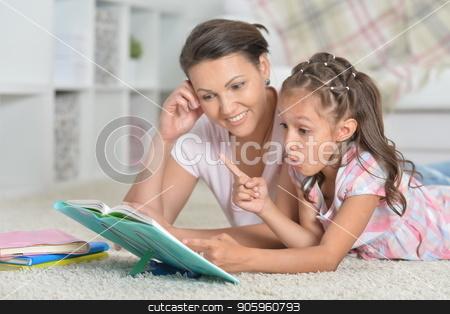 Mother with daughter doing homework stock photo, Close-up portrait of mother with daughter doing homework by Ruslan Huzau