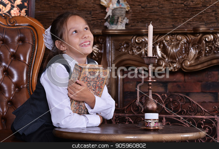 little girl reading book  stock photo, Cute little girl in school uniform holding book in room with vintage furniture by Ruslan Huzau