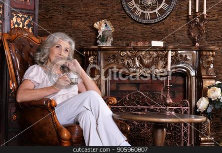 Senior woman with coffee in chair stock photo, portrait of senior  woman with coffee in chair by Ruslan Huzau