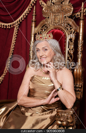 senior woman sitting in vintage chair stock photo, Beautiful senior woman in golden dress with crown sitting in vintage chair by Ruslan Huzau