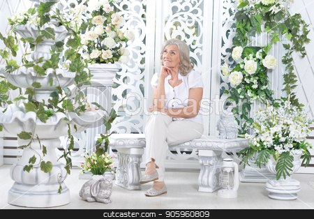 Beautiful senior woman posing in light room decorated with white stock photo, Beautiful senior woman posing in light room decorated with white flowers by Ruslan Huzau