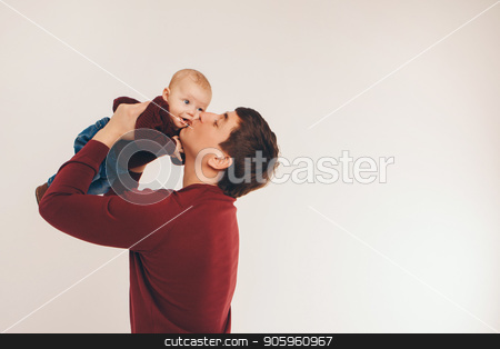 Adult man giving a kiss to his baby raised in his arms. stock photo, Adult man giving a kiss to his baby raised in his arms. by aaalll3110