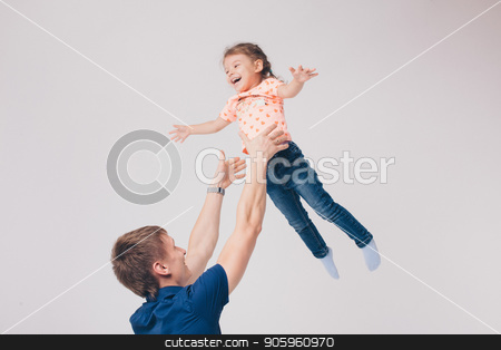 Dad raised his daughter in his arms on a white background. Girl in fly stock photo, Dad raised his daughter in his arms on a white background. Girl in fly by aaalll3110