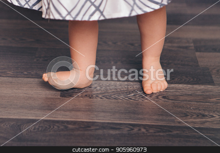 Cropped photo: barefoot child standing on the floor. The first steps in close-up. Healthy baby feet stock photo, Cropped photo: barefoot child standing on the floor. The first steps in close-up. Healthy baby feet by aaalll3110