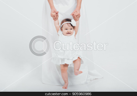 a little girl in a white dress learns to walk holding her mother's hands. Newborn fashion stock photo, a little girl in a white dress learns to walk holding her mother's hands. Newborn fashion by aaalll3110