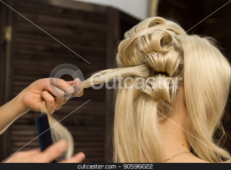 Hairdresser does hairstyle for luxurious blond woman. coiffure in the form of big curl. Concept wedding hairstyle stock photo, Hairdresser does hairstyle for luxurious blond woman. coiffure in the form of big curl. Concept wedding hairstyle. by Alexander