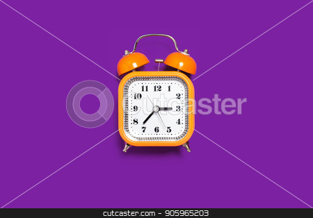 orange alarm clock on the purple background stock photo, Vintage style orange metal alarm clock with bells standing on the purple surface isolated. back to school concept. free space for text by Oleh