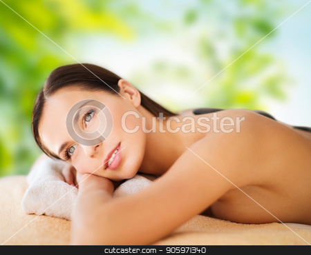 beautiful woman having hot stone therapy at spa stock photo, wellness, spa and beauty concept - beautiful woman having hot stone therapy over green natural background by Syda Productions