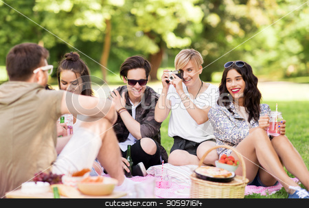 friends with camera photographing at summer picnic stock photo, friendship, leisure and technology concept - group of happy smiling friends with non alcoholic drinks photographing by vintage camera at picnic in summer park by Syda Productions