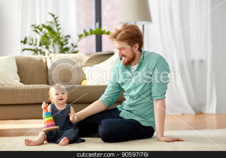 father playing with little baby daughter at home stock photo, family, fatherhood and people concept - happy red haired father with ball playing with little baby daughter at home by Syda Productions