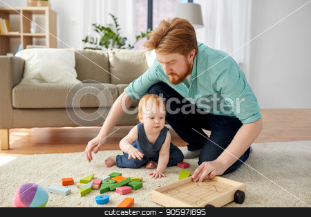 father and baby playing with toy blocks at home stock photo, family, fatherhood and people concept - happy red haired father and little baby daughter playing with toy blocks kit at home by Syda Productions