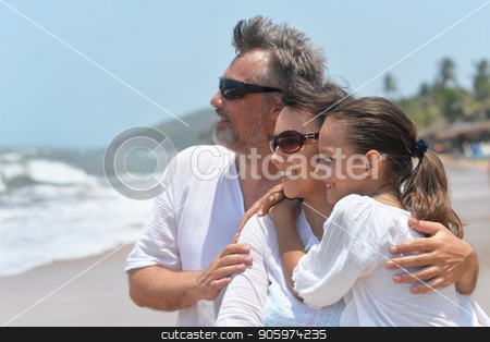 Portrait of a happy family hugging on sandy beach and looking at sea stock photo, happy family hugging on sandy beach and looking at sea by Ruslan Huzau