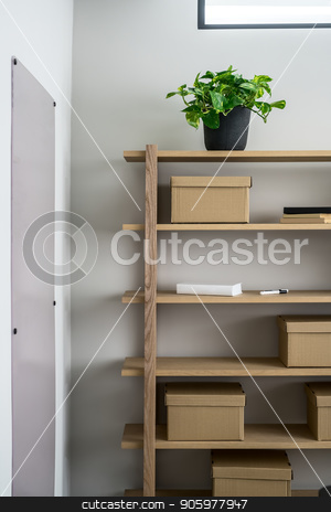 Stylish interior with wooden shelves and gray walls stock photo, Wooden shelves on the gray wall background in the luminous interior. On them there are cardboard boxes, green plant in the pot, books and markers. On the walls there is a board and a mirror. Closeup. by bezikus
