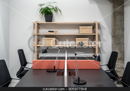 Stylish office in loft style with gray walls stock photo, Illuminated interior in an office with gray walls and a concrete column. There are wooden shelves with cardboard boxes and green plant and books, black table with a peach partition and lamps, chairs. by bezikus