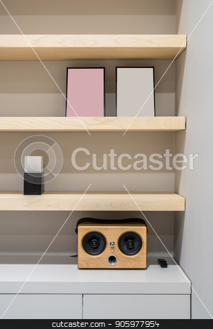 Stylish interior with wooden shelves and gray walls stock photo, Light wooden shelves on the gray wall background in a luminous office. There is a speaker with a black remote controller, frames, lockers. Closeup. Vertical. by bezikus