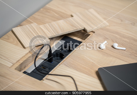 Closeup photo of wooden table with power sockets stock photo, Black power sockets built-in the light wooden table on the gray wall background. On the table there is a laptop with a power cable and white wireless earphones. Closeup. Horizontal. by bezikus