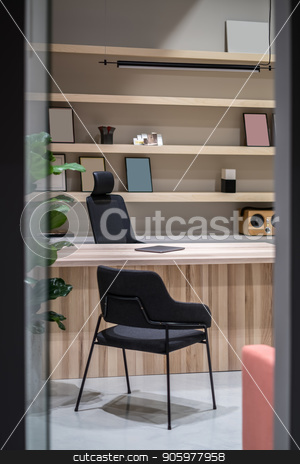 Stylish office with wooden table and shelves stock photo, Room in a luminous office with gray walls. There is a wooden table with a laptop, black chairs, green plant, hanging lamp, wooden shelves with frames and a speaker and books. Vertical. by bezikus