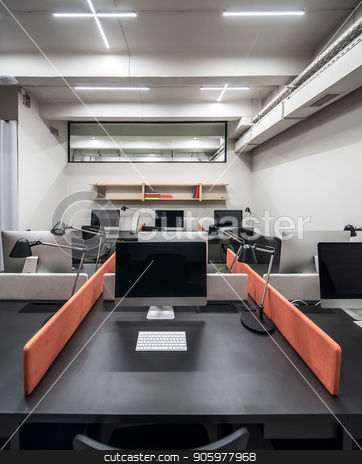 Stylish office in loft style with light walls stock photo, Nice luminous interior in an office in a loft style with light walls. There are black tables with peach partitions, dark chairs, computers, lamps, wooden shelves with books, glass partition on a wall. by bezikus