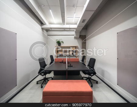 Stylish office in loft style with gray walls stock photo, Luminous interior in an office with gray walls and a concrete column. There are wooden shelves with boxes and green plant and books, black table with a peach partition and lamps, chairs, pouf, boards. by bezikus