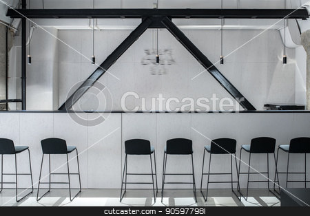 Stylish interior in loft style with gray walls stock photo, Nice bar with a rack and black wooden partitions in a luminous interior in a loft style with gray walls and concrete columns. There are several dark chairs, hanging lamps. Horizontal. by bezikus