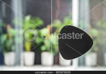 Black handle on glass door in luminous interior stock photo, Closeup low aperture photo of the glass door with a black handle on the background of the green plants in the big pots. Horizontal. by bezikus