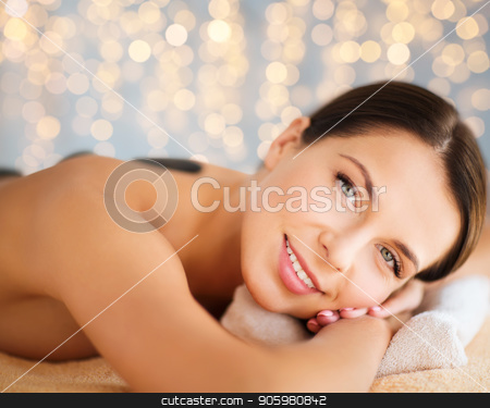 beautiful woman having hot stone therapy at spa stock photo, wellness, spa and beauty concept - beautiful woman having hot stone therapy over holidays lights background by Syda Productions