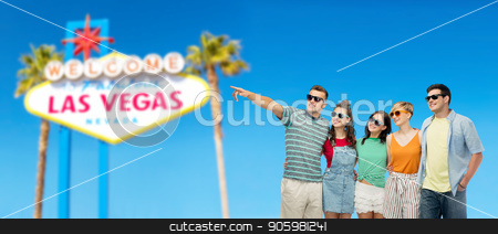 friends in sunglasses stock photo, entertainment, leisure and friendship concept - group of happy smiling friends in sunglasses pointing finger to something over welcome to fabulous las vegas sign background by Syda Productions