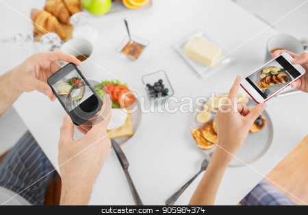 close up of couple with smartphones at breakfast stock photo, food and technology concept - close up of couple with smartphones having breakfast at home by Syda Productions