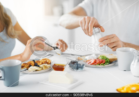 close up of couple having breakfast at home stock photo, food and eating concept - close up of couple having breakfast at home by Syda Productions