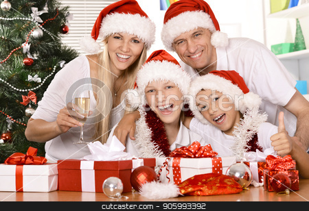 big happy family in santa hats stock photo, big happy family at new years eve posing in santa hats with gifts by Ruslan Huzau