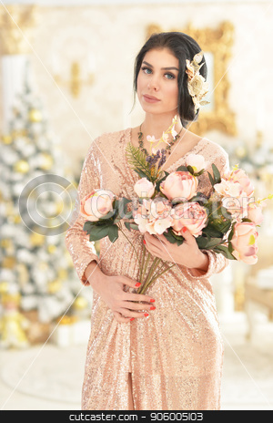 Portrait of beautiful young woman with flowers stock photo, Portrait of beautiful young woman with flowers posing in room decorated to Christmas holiday by Ruslan Huzau