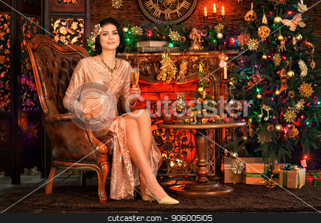 Portrait of beautiful young woman in golden dress posing stock photo, Portrait of beautiful young woman in golden dress posing in room decorated to Christmas holiday by Ruslan Huzau