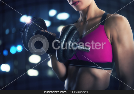 Athletic woman training biceps at the gym stock photo, Athletic muscular woman training biceps with dumbbells at the gym by Federico Caputo