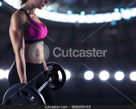 Athletic woman training biceps at the gym stock photo, Athletic muscular woman training biceps with barbell at the gym by Federico Caputo