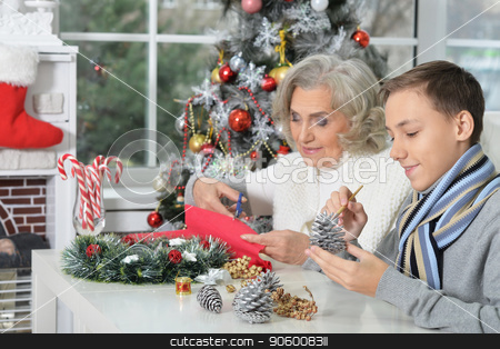 Portrait of happy grandmother with her grandson stock photo, Portrait of happy grandmother with her grandson preparing for Christmas by Ruslan Huzau