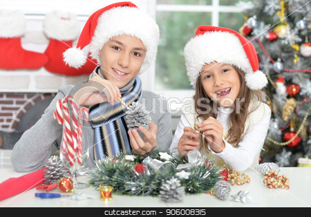 Happy brother and sister in Santa hats preparing for Christmas stock photo, Portrait of happy brother and sister in Santa hats preparing for Christmas by Ruslan Huzau