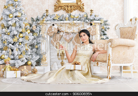Portrait of beautiful young woman posing in room stock photo, Portrait of beautiful young woman posing in room decorated to Christmas holiday by Ruslan Huzau