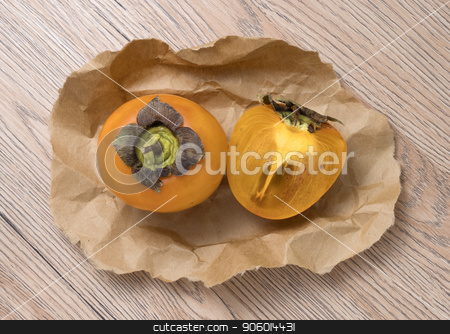 Delicious ripe persimmon fruit on wooden background. stock photo, Delicious ripe persimmon fruit on craft paper, on wooden background. by Valery Kraynov
