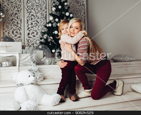 Mother and child hugging white teddy bear and posing stock photo, Front view of cute family sitting together on stairs, looking at camera and smiling at christmas. Beautiful mother and child hugging big white teddy bear. Concept of new year atmosphere. by studiolucky