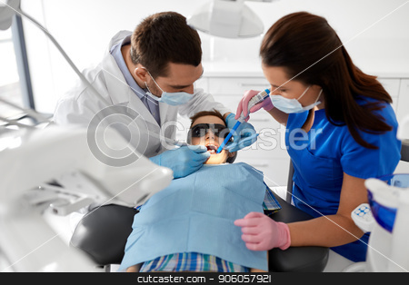 dentist treating kid teeth at dental clinic stock photo, medicine, dentistry and healthcare concept - dentist and assistant with dental drill and saliva ejector treating kid patient teeth at dental clinic by Syda Productions